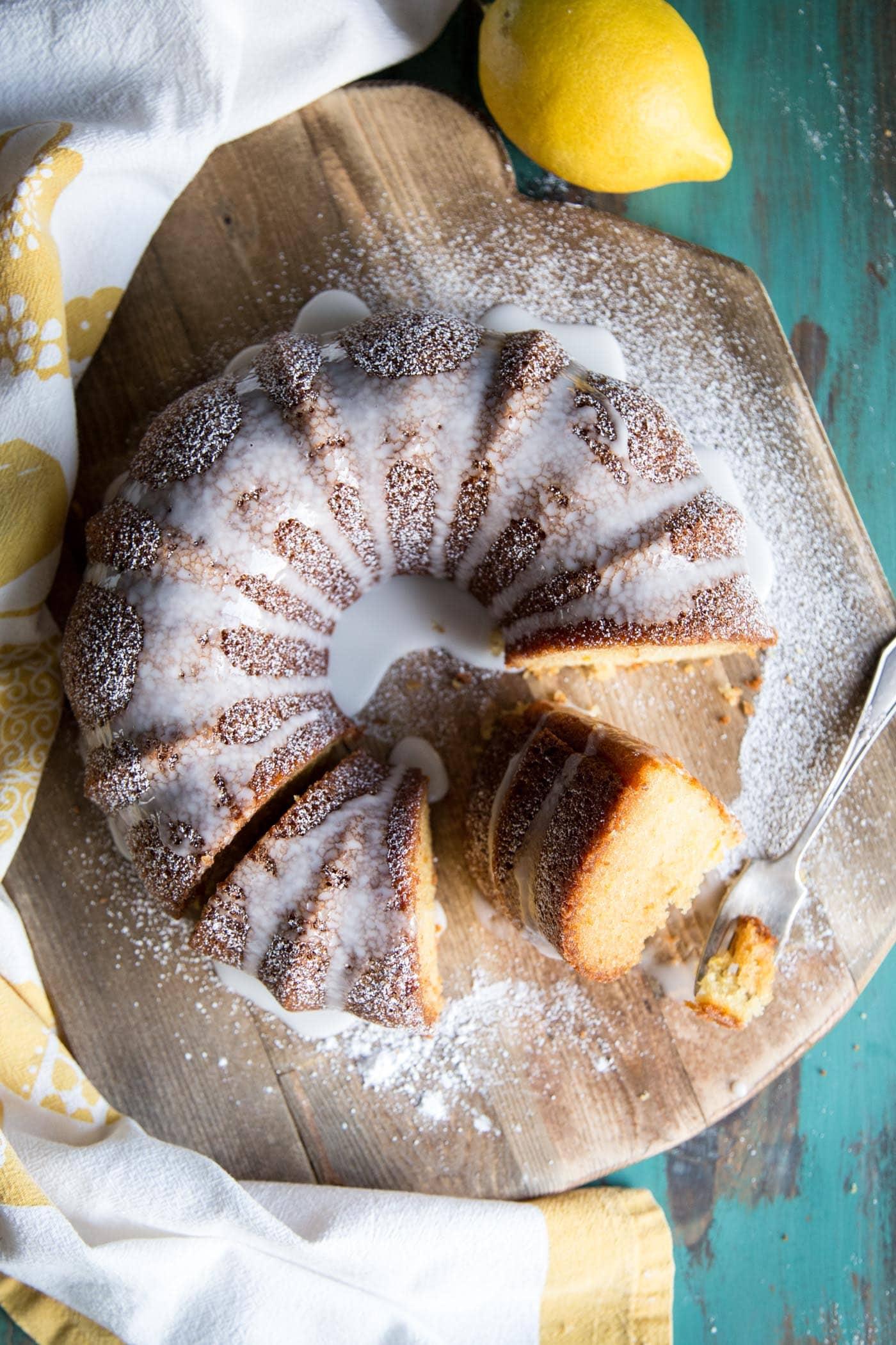 Lemon bundt cake with glaze on a wooden board