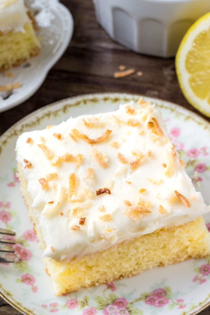 A slice of lemon cake with fluffy coconut frosting topped with toasted coconut.