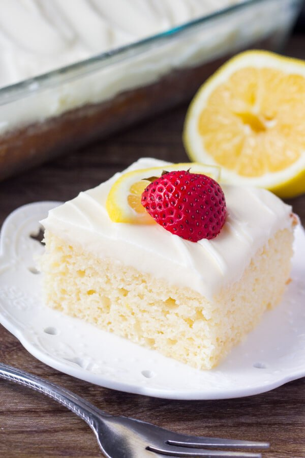 slice of lemon cake topped with lemon frosting on white plate