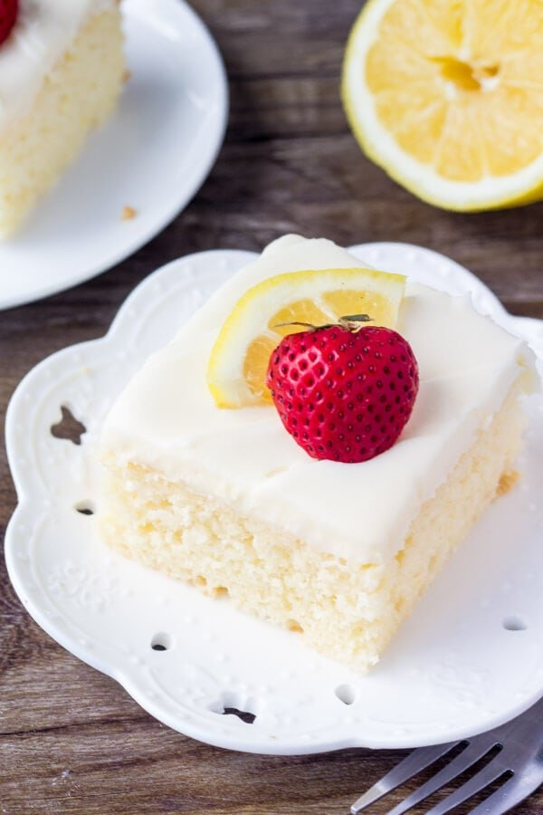slice of homemade lemon cake with lemon cream cheese frosting on white plate