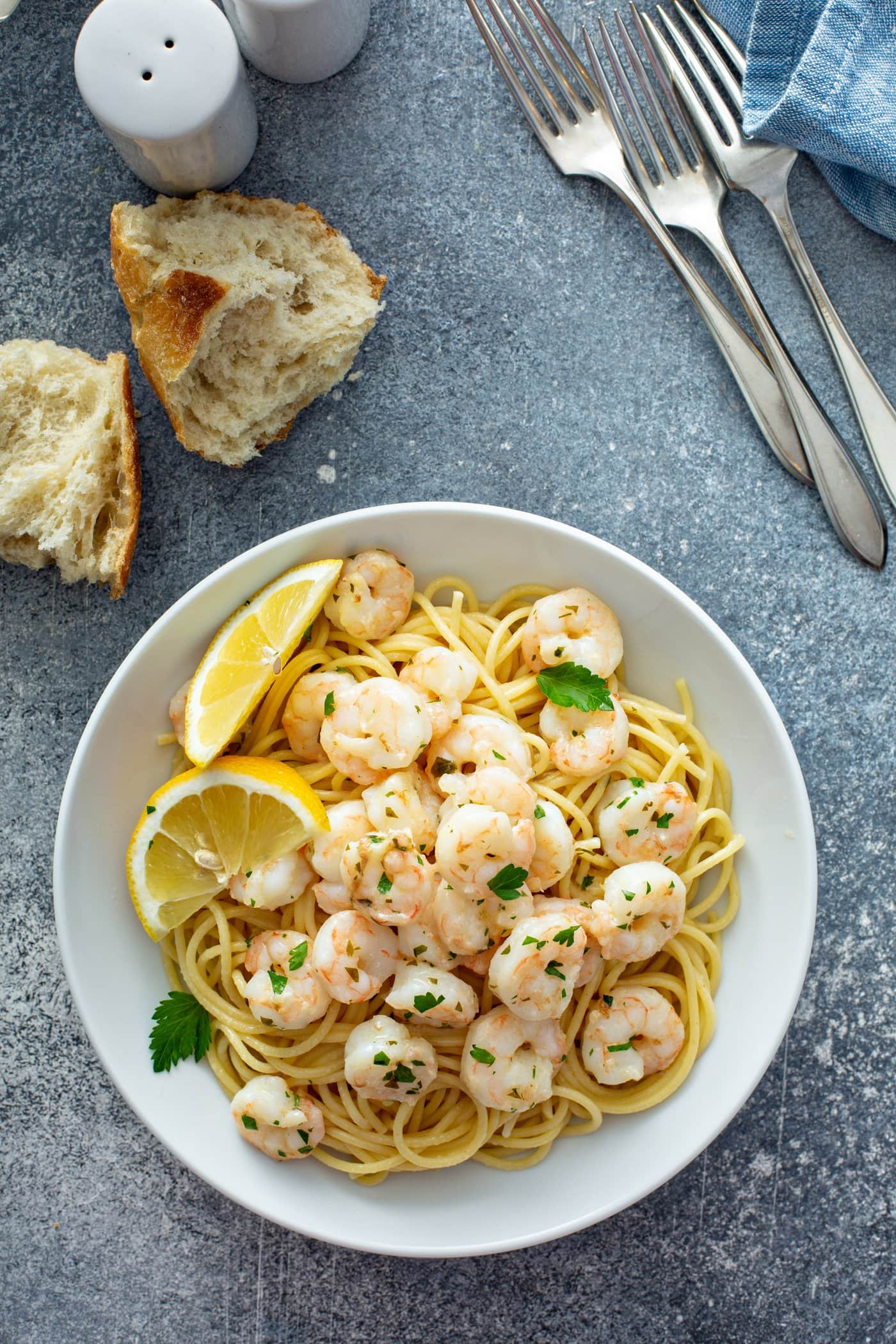 A bowl of lemon garlic shrimp over pasta. there are two lemon wedges on the edge of the bowl and the shrimp is sprinkled with fresh parsley. There are two pieces of torn bread and three forks in the background.