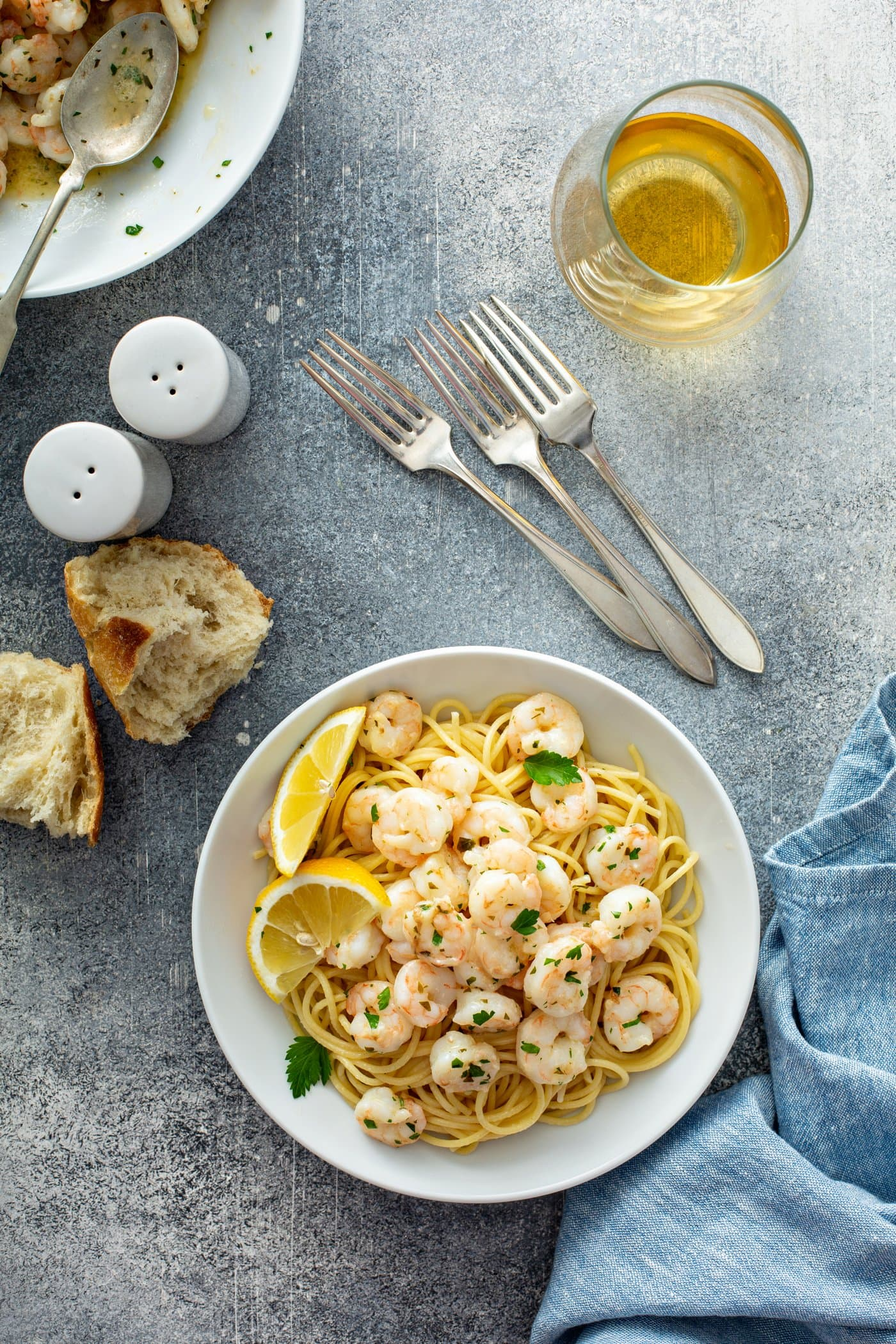 A serving dish of lemon garlic shrimp over pasta. There are lemon wedges on the edge of the plate and the shrimp are sprinkled with fresh parsley. There is a container of oil, three forks, salt and pepper shakers, and two pieces of hard bread in the background.
