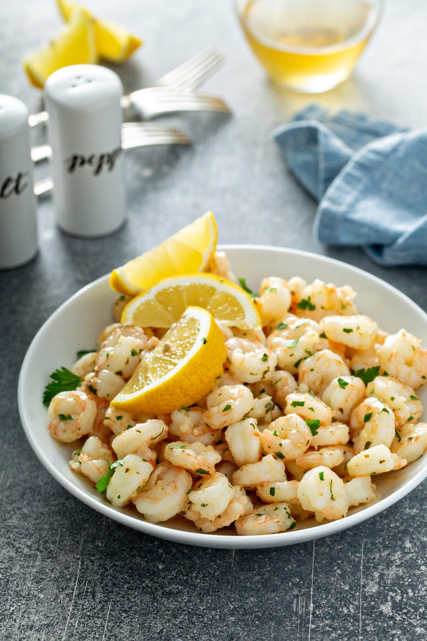 A white dish filled with lemon garlic shrimp. There are three lemon wedges on top of the shrimp and it is all sprinkled with fresh parsley. There is a blue napkin and white salt and pepper shakers in the background.