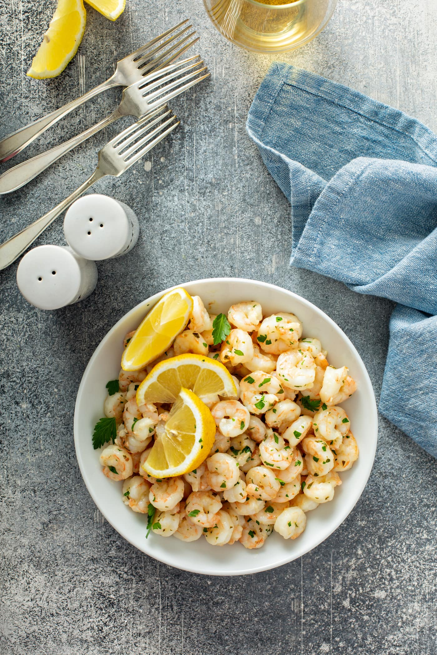 A serving plate of lemon garlic shrimp. There are three lemon wedges on top of the shrimp and fresh parsley is sprinkled over the dish. There is a blue napkin, three forks and salt and pepper shakers on the table.