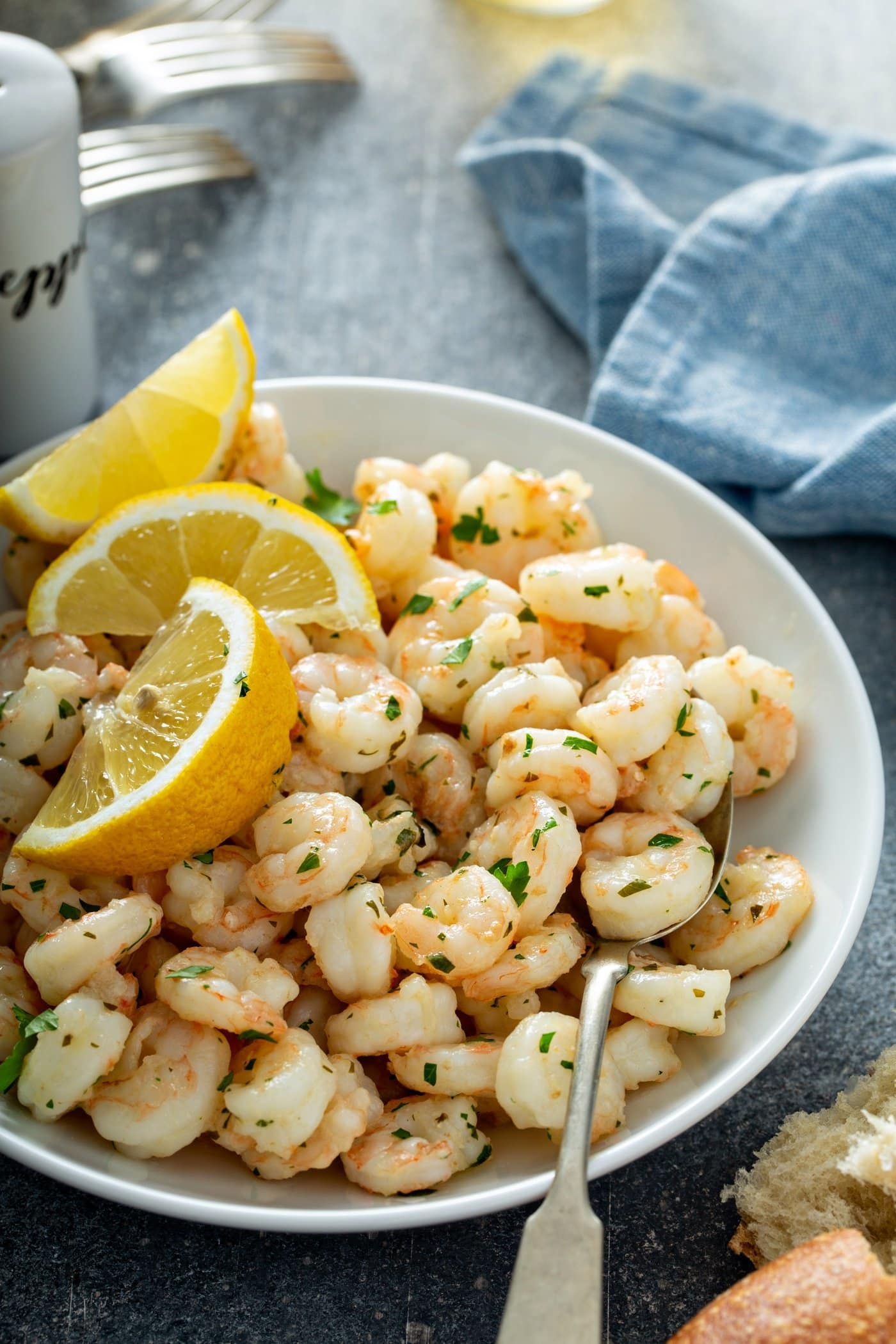 A serving plate of lemon garlic shrimp with three lemon wedges and fresh parsley on top. A napkin and salt and pepper shaker are in the background.
