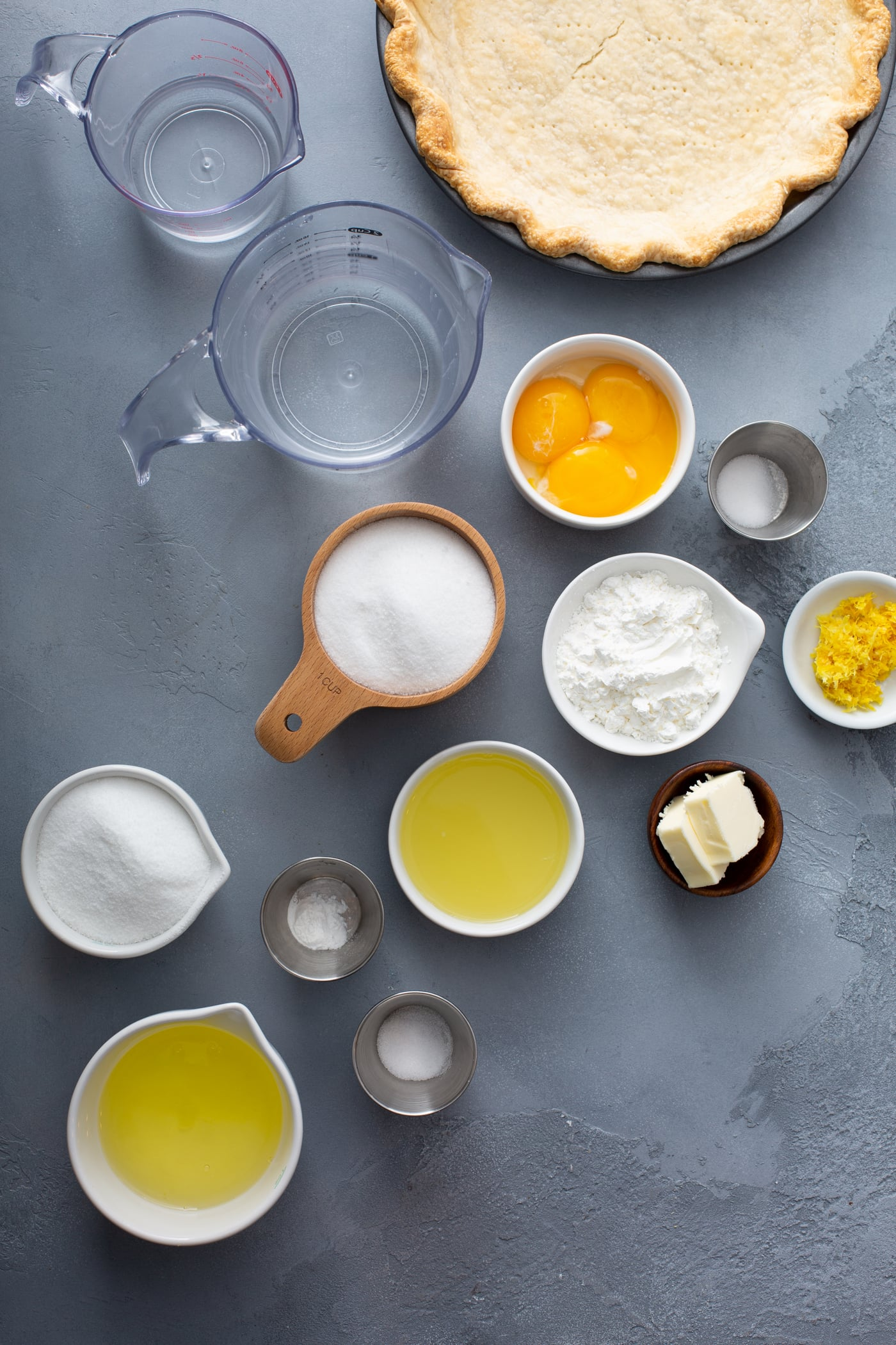 a picture of measuring cups with ingredients for lemon meringue pie. there are containers of eggs, water, sugar, salt lemon juice, lemon zest, butter, etc.