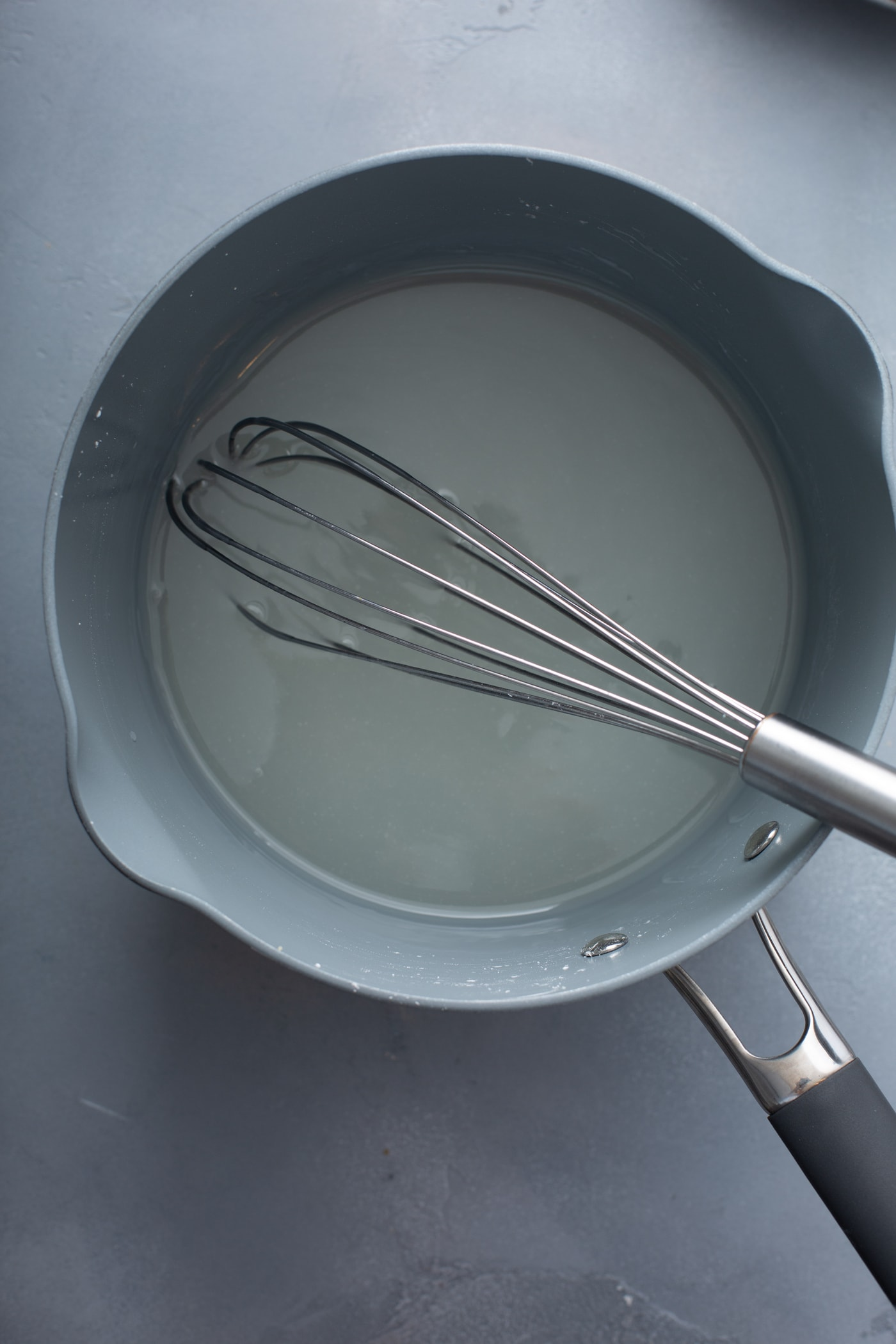A saucepan with water and sugar and a whisk.