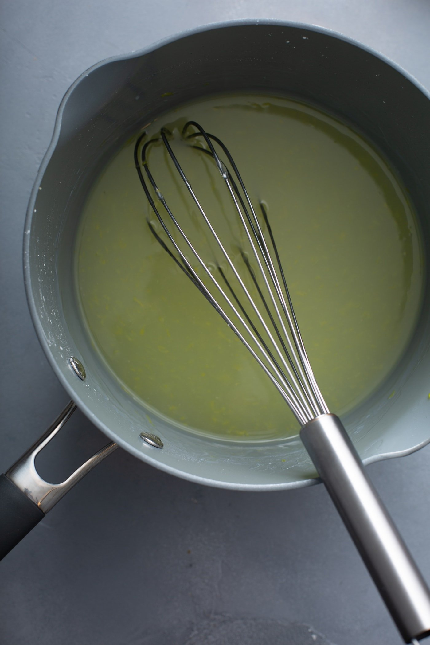 A sauce pan with lemon pie filling in it. It has a whisk resting in the filling.