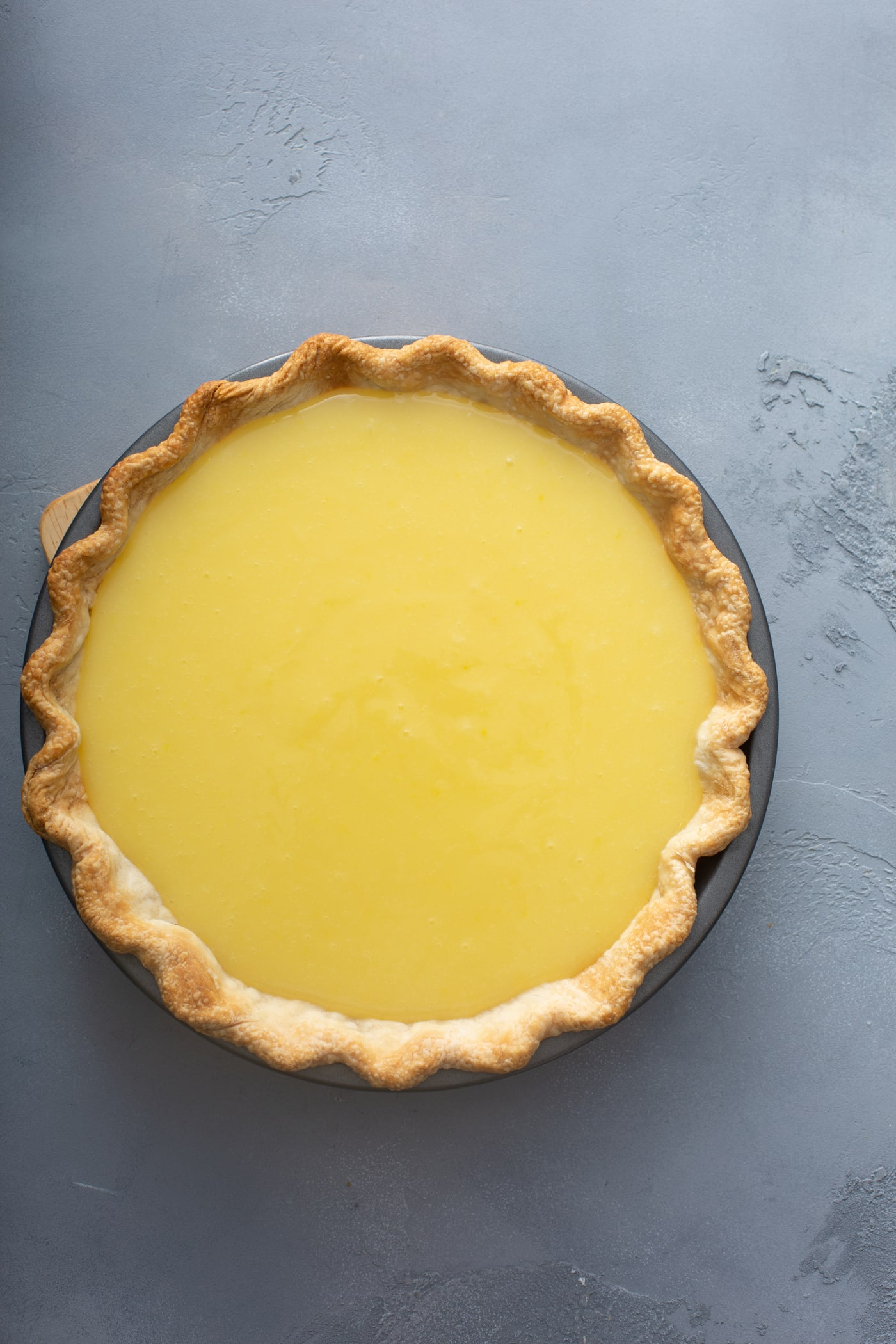 A picture or a lemon pie. The filling is bright yellow and the crust is light golden brown.