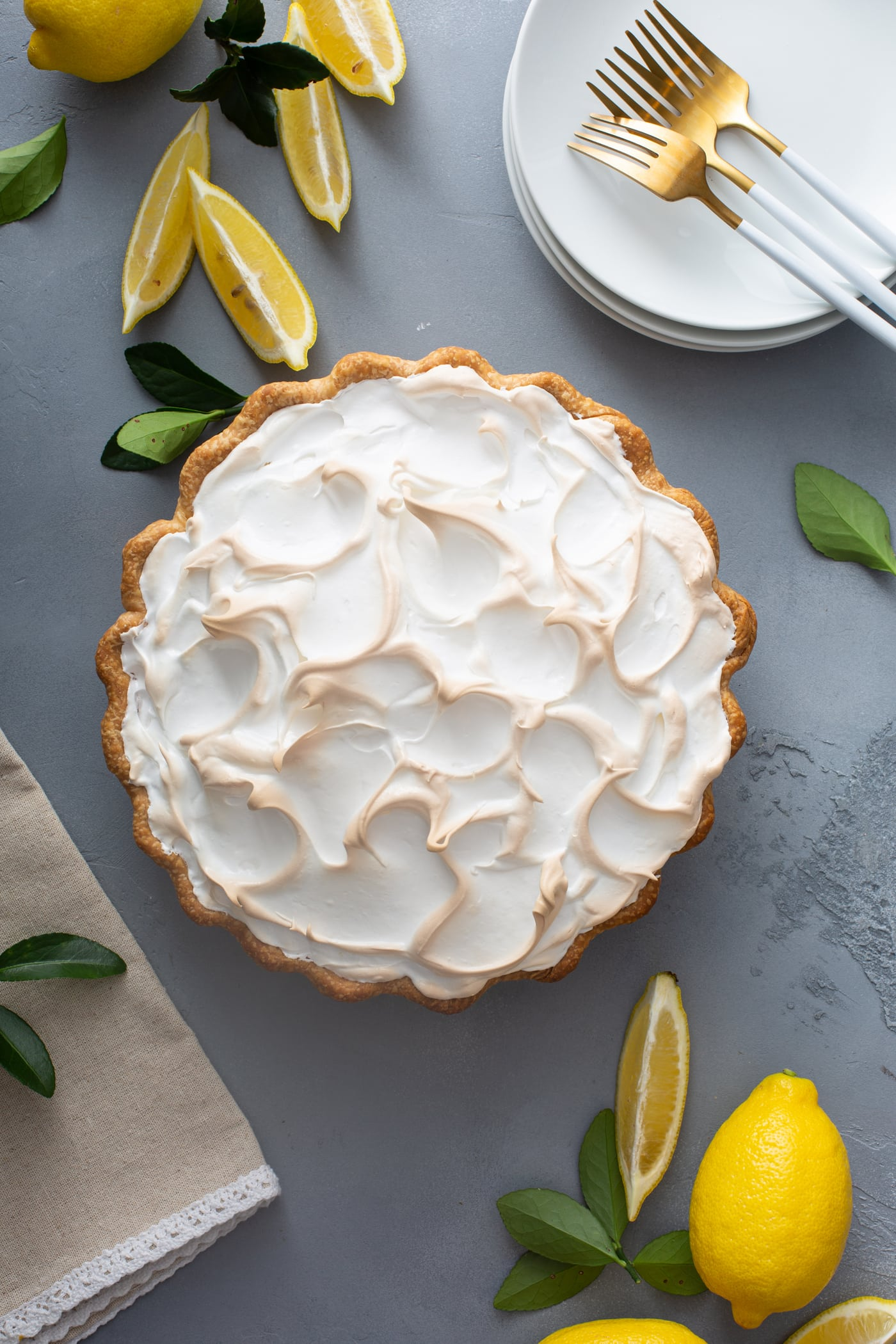 A picture of a lemon meringue pie. the meringue is fluffy and slightly browned. There are lemon wedges next to the pie.