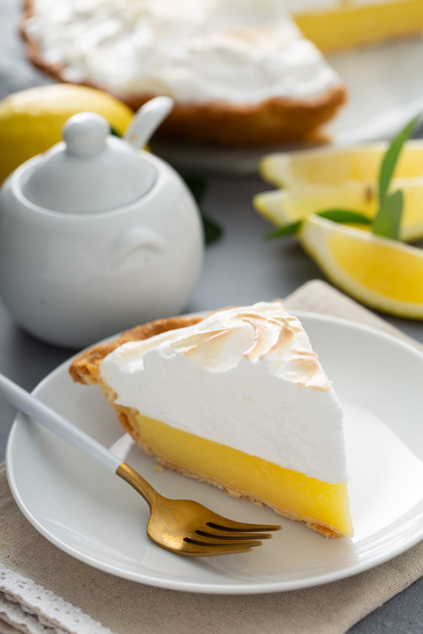 A picture of a slice of lemon meringue pie. The filling is bright yellow and the meringue on top is lightly toasted. There are lemon wedges and a sugar bowl in the background and a fork is on the plate next to the slice of pie.