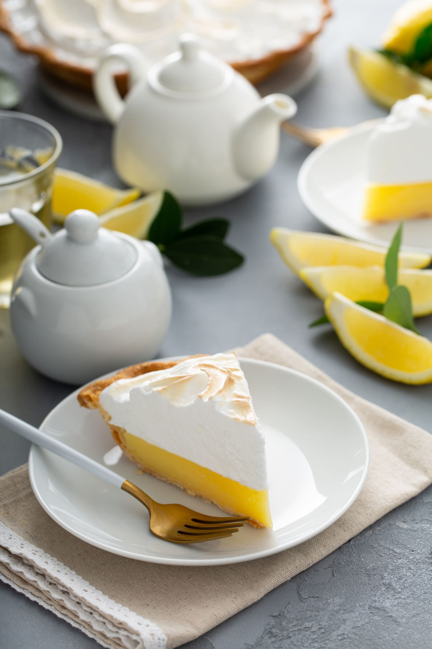 A piece of lemon meringue pie on a dessert plate. A fork in next to the pie and there are lemon wedges and a sugar bowl and cream pitcher in the background.