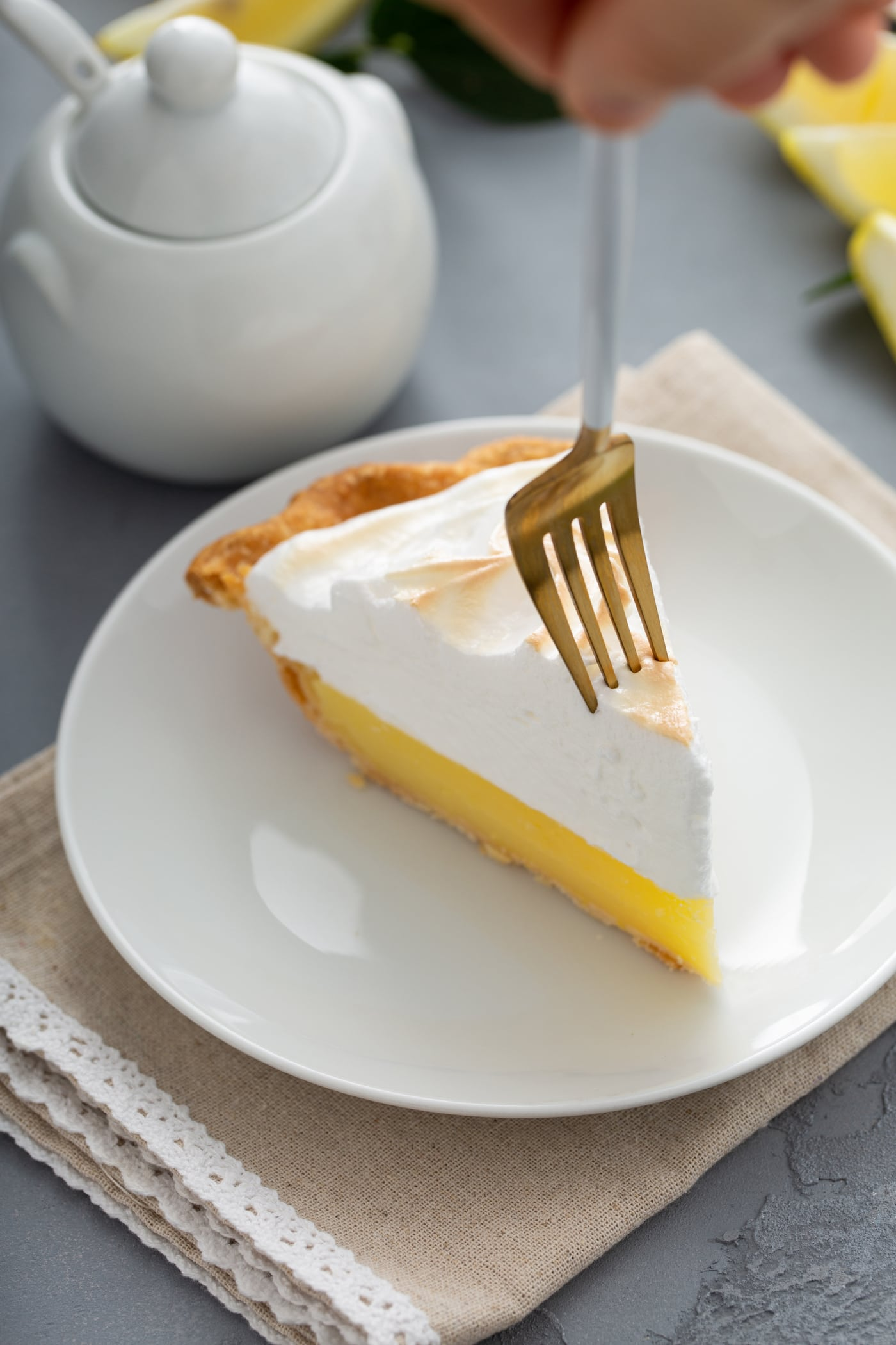 A piece of lemon meringue pie. A fork is piercing the tip of the slice.