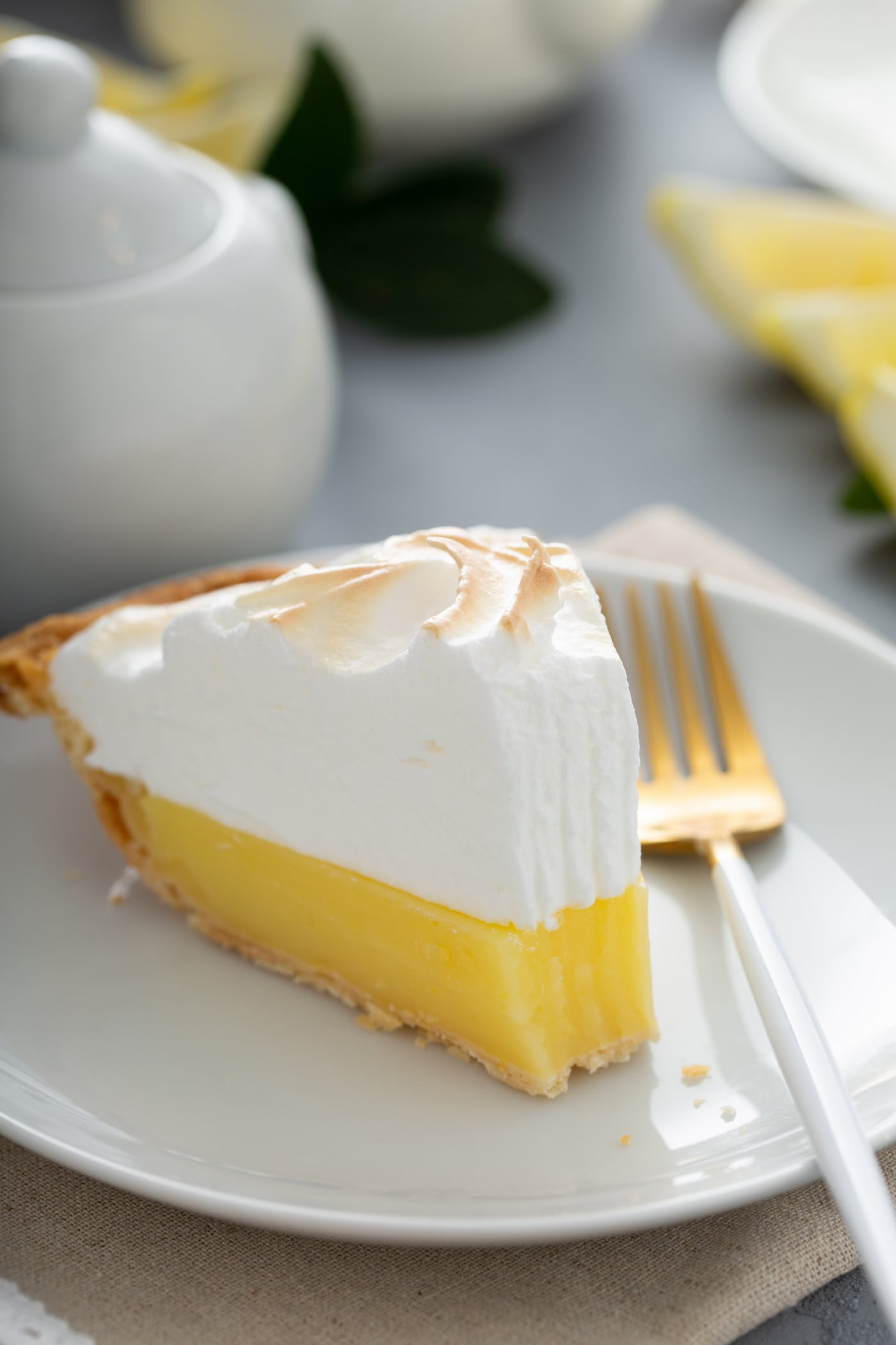 A slice of lemon meringue pie on a white dessert plate. A fork is next to the pie, and one bite has been taken from the slice.