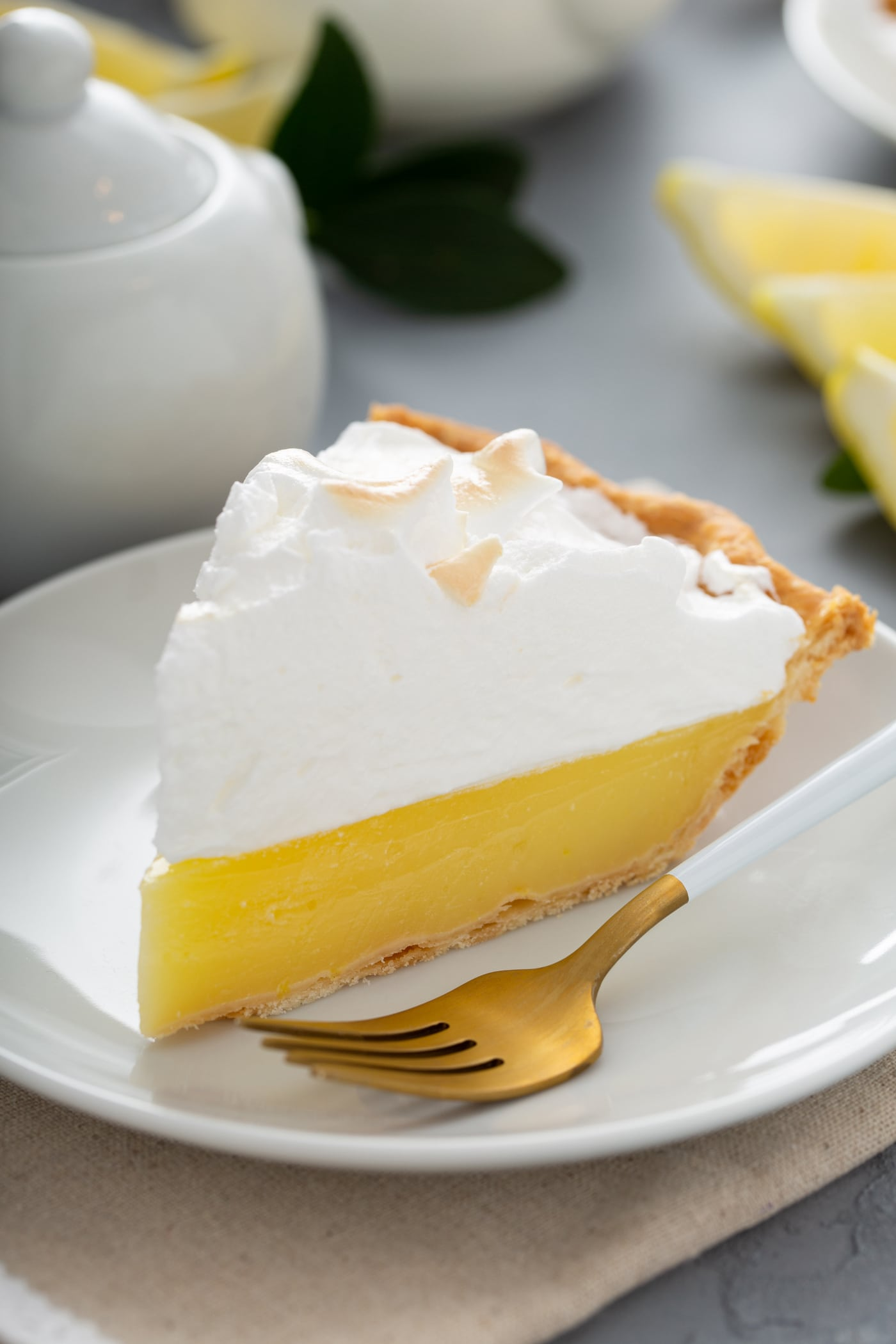 A slice of lemon meringue pie on a white dessert plate. A fork is next to the slice of pie. The filling is bright yellow and the meringue is lightly toasted.