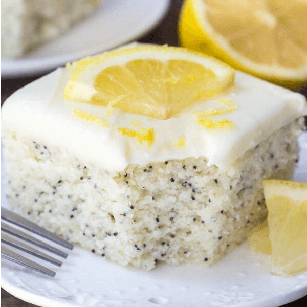 This Lemon Poppy Seed Cake with Cream Cheese Frosting is soft, moist & deliciously buttery with a fresh lemon flavor. Dotted with poppy seeds & topped with cream cheese frosting - it's the perfect dessert for lemon lovers! ohsweetbasil.com