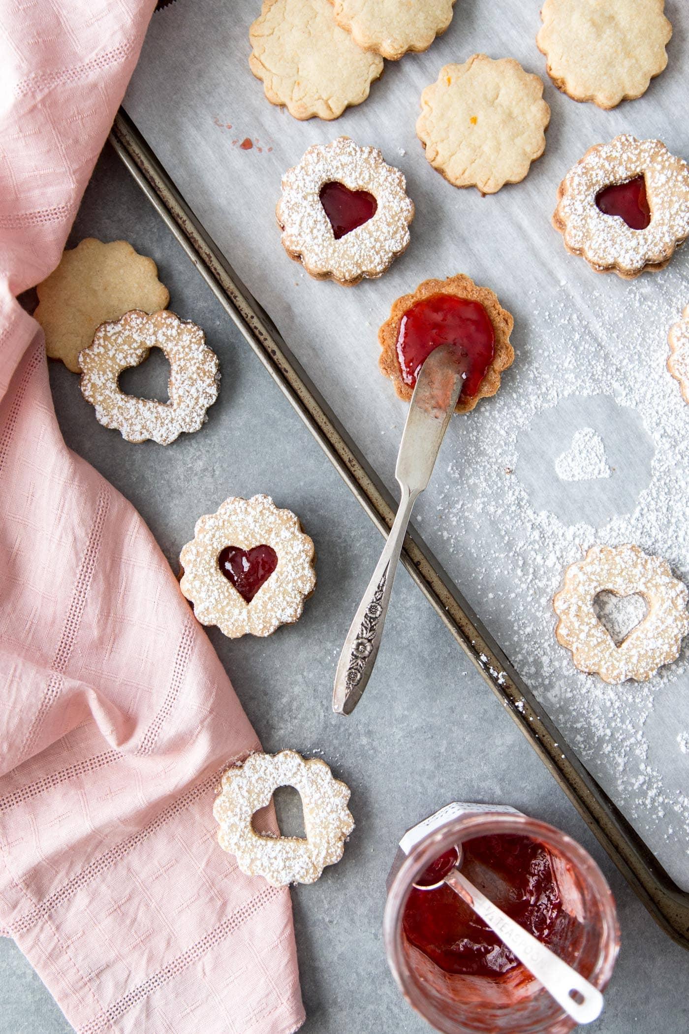 Adding strawberry jam to Linzer cookies