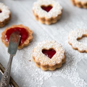 Linzer cookies with strawberry jam filling on a baking sheet
