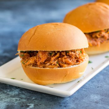 Two Slow Cooker Pulled Pork Sandwiches on a white serving platter.