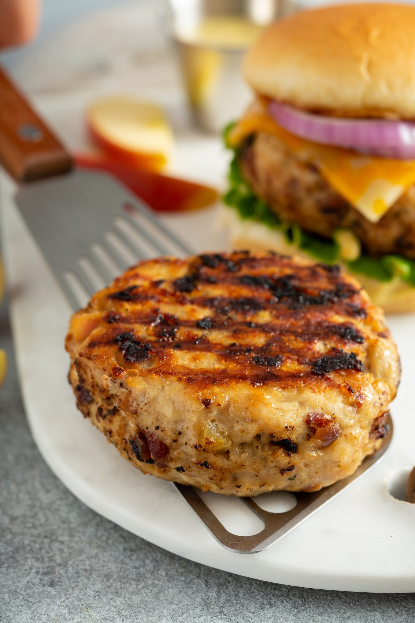 A grilled chicken burger patty being placed on a white plate with a spatula. There are apple slices and another chicken burger in the background..