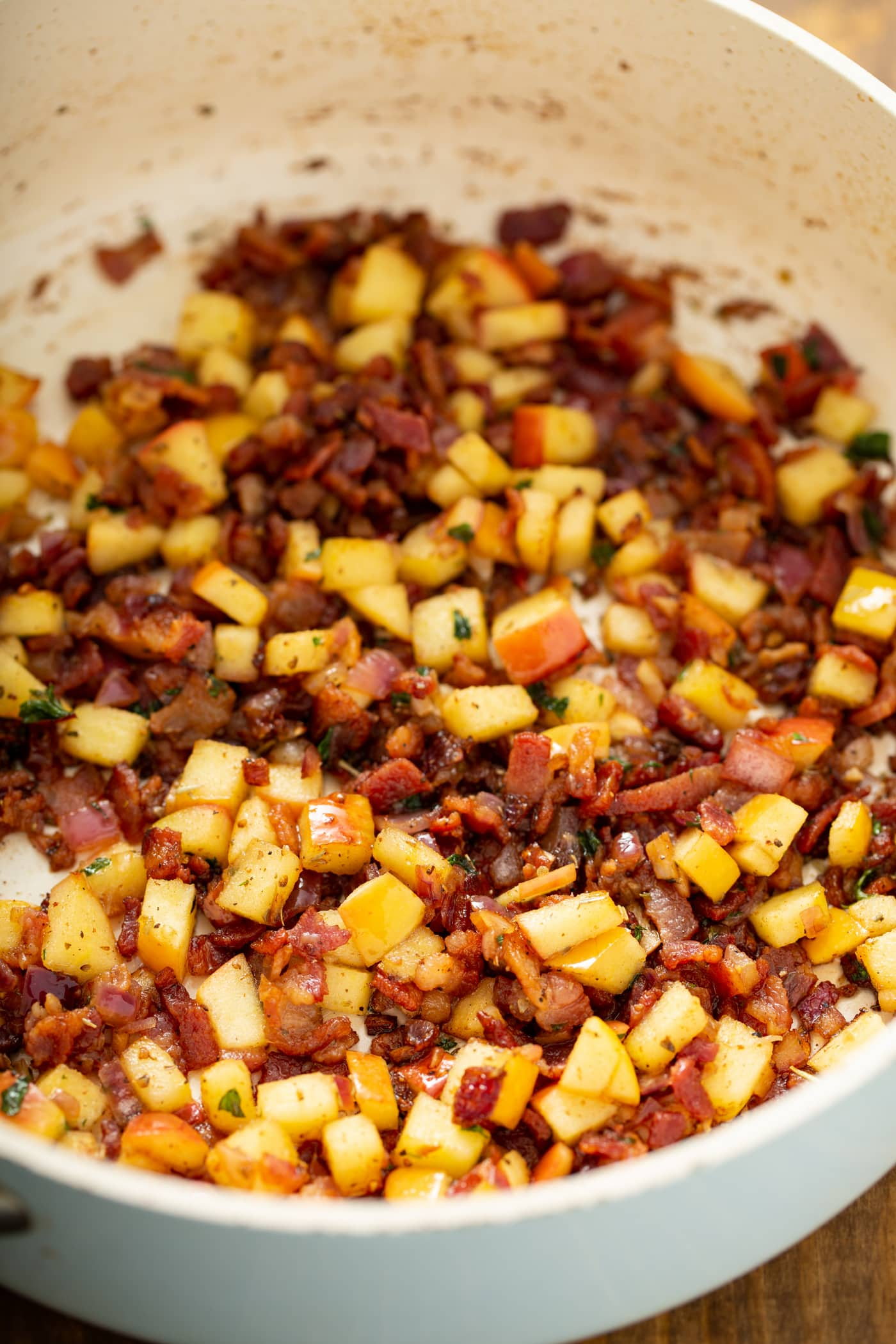 A skillet filled with cooked bacon, apples, onions, spices,and herbs.
