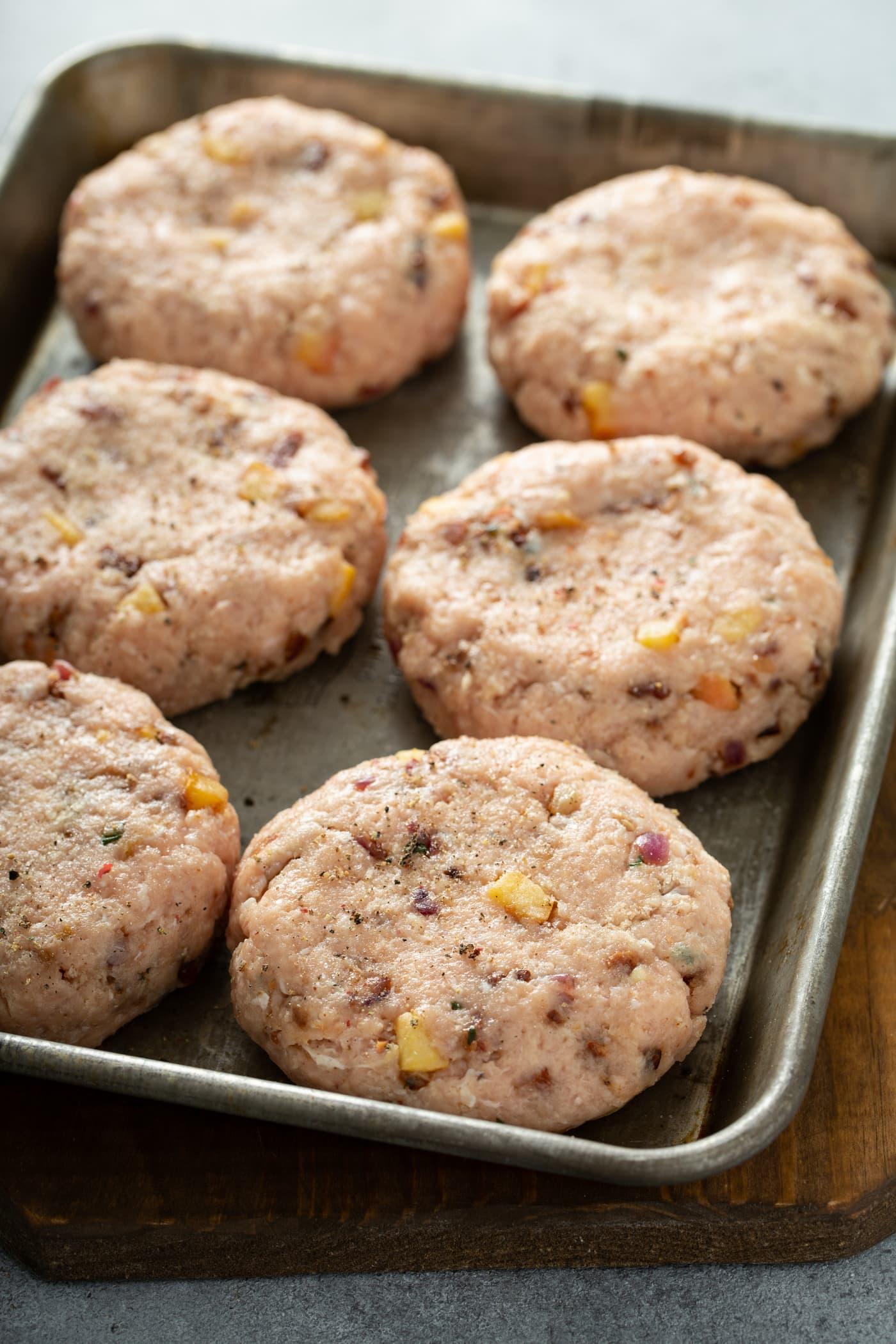 6 chicken burger patties on a baking pan.