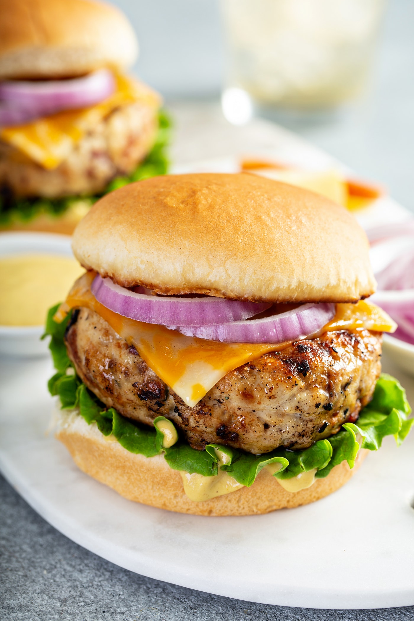 A chicken burger on a bun with lettuce, cheese, and red onion. There is another chicken burger in the background and small containers of bread crumbs, and red onions.