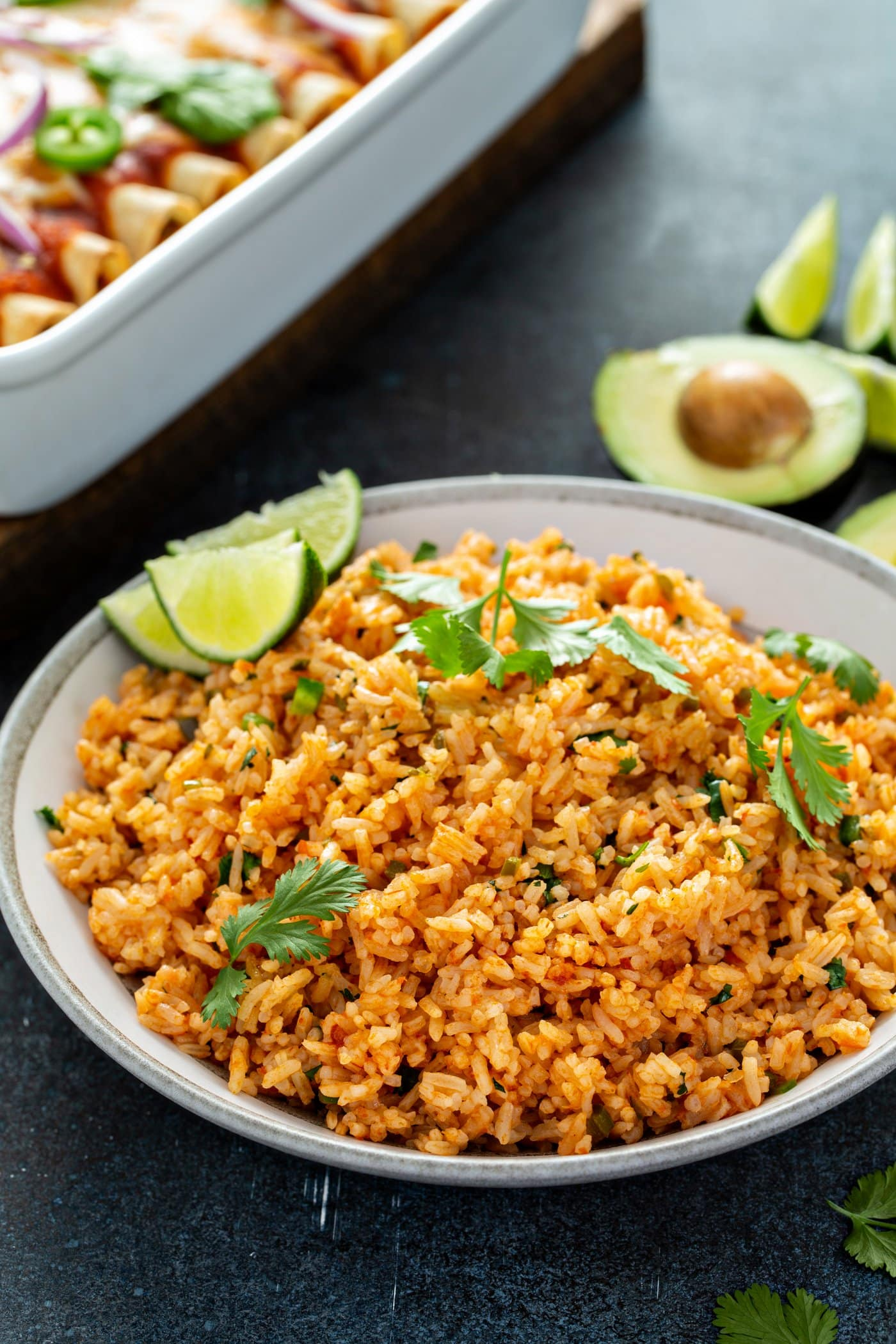 A bowl of Spanish rice. It has cilantro leaves sprinkled on top and three lime wedges on the edge. There is an avocado that has been cut in half and a baking dish of enchiladas in the background.