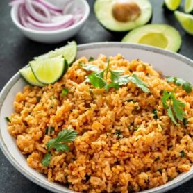 A bowl of Spanish rice with cilantro leaves sprinkled on top. there are three lime wedges on the edge of the bowl and a bowl of sliced red onion and an avocado that has been cut in half and two forks and two spoons in the background.