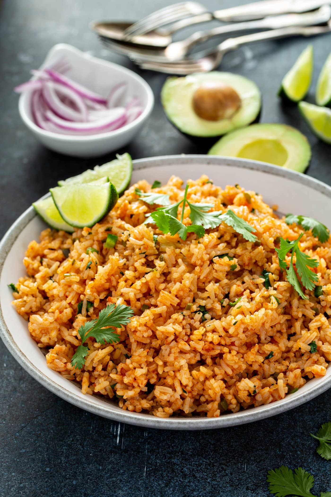 A bowl of Spanish rice with cilantro leaves sprinkled on top. there are three lime wedges on the edge of the bowl and a bowl of sliced red onion and an avocado that has been cut in half in the background.