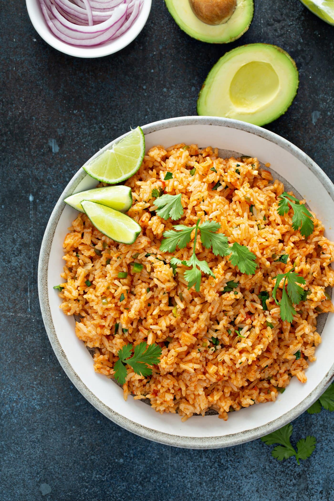 A serving bowl of Spanish rice topped with cilantro leaves and three lime wedges. There is a halved avocado in the background.