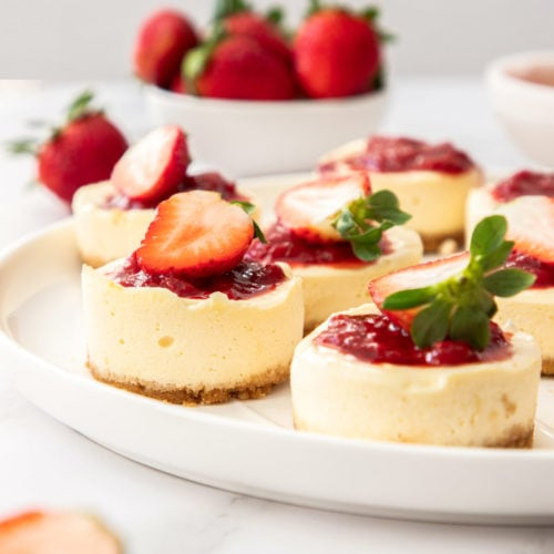 A large white plate with a batch of mini strawberry cheesecakes on it