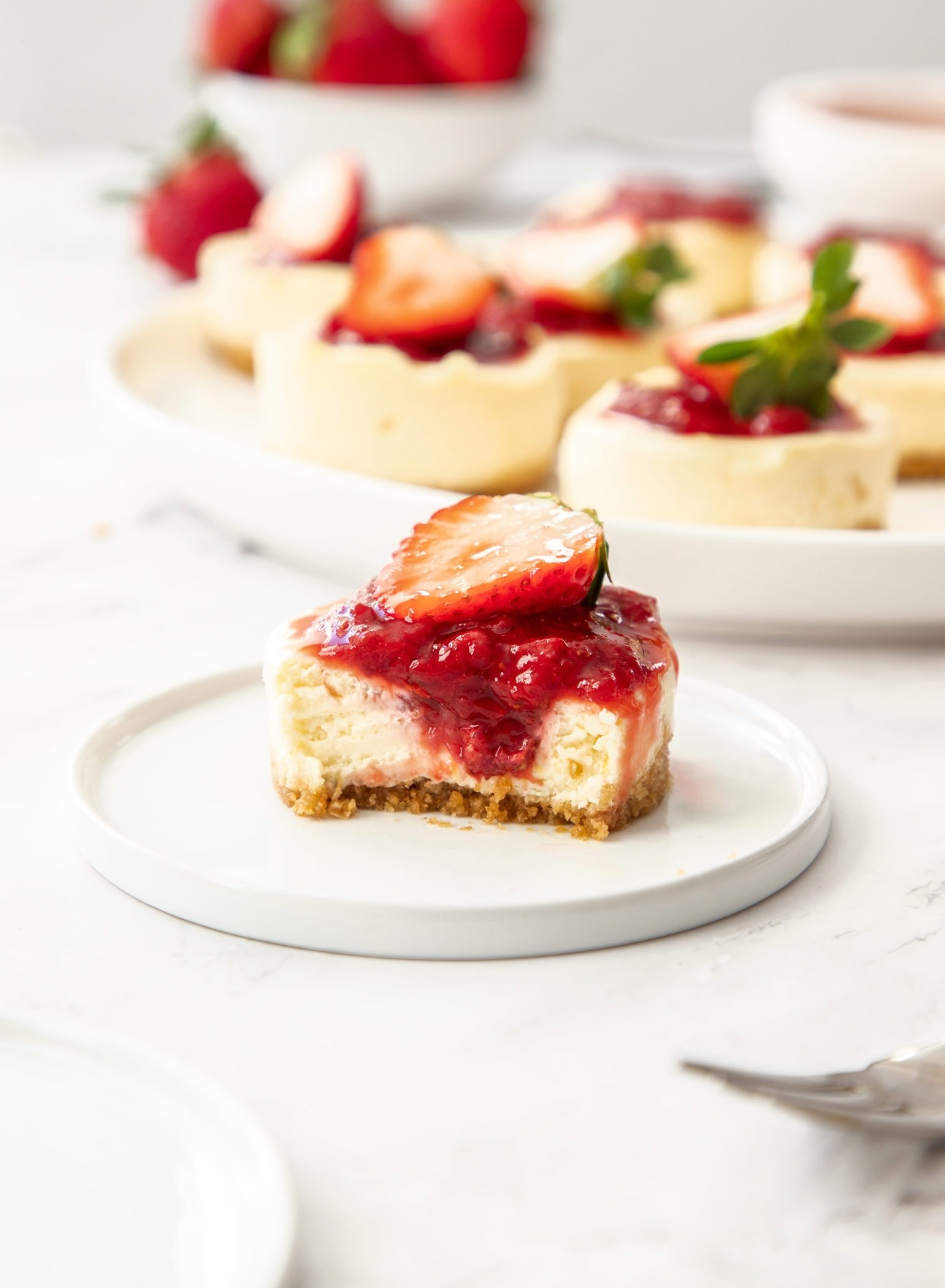 A mini cheesecake on a small white plate, with more in the background