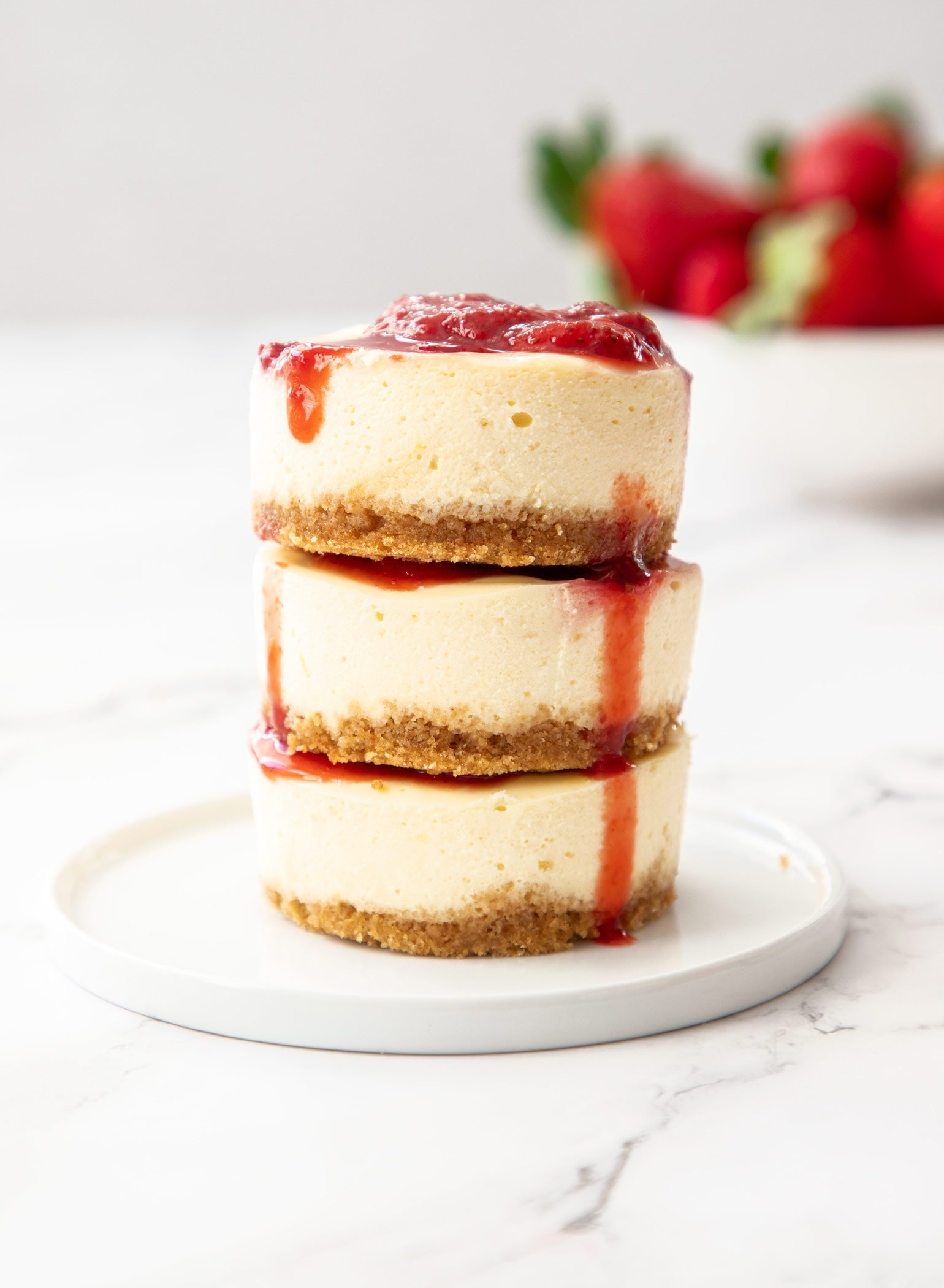 3 mini strawberry cheesecakes stacked on top of each other on a small white plate