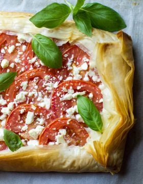 This Mozzarella Tomato Tart has a butter-garlic phyllo crust with mozzarella, tomatoes, feta, and basil. Makes a great appetizer or light meal for summer!