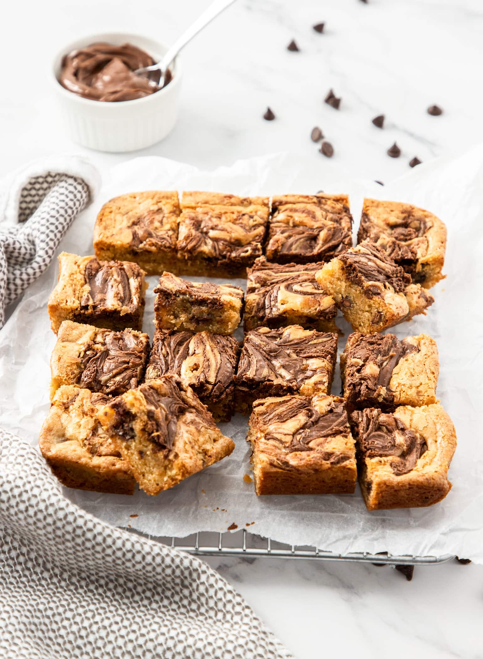 A batch of blondies on a sheet on baking paper with a small bowl of nutella in the background