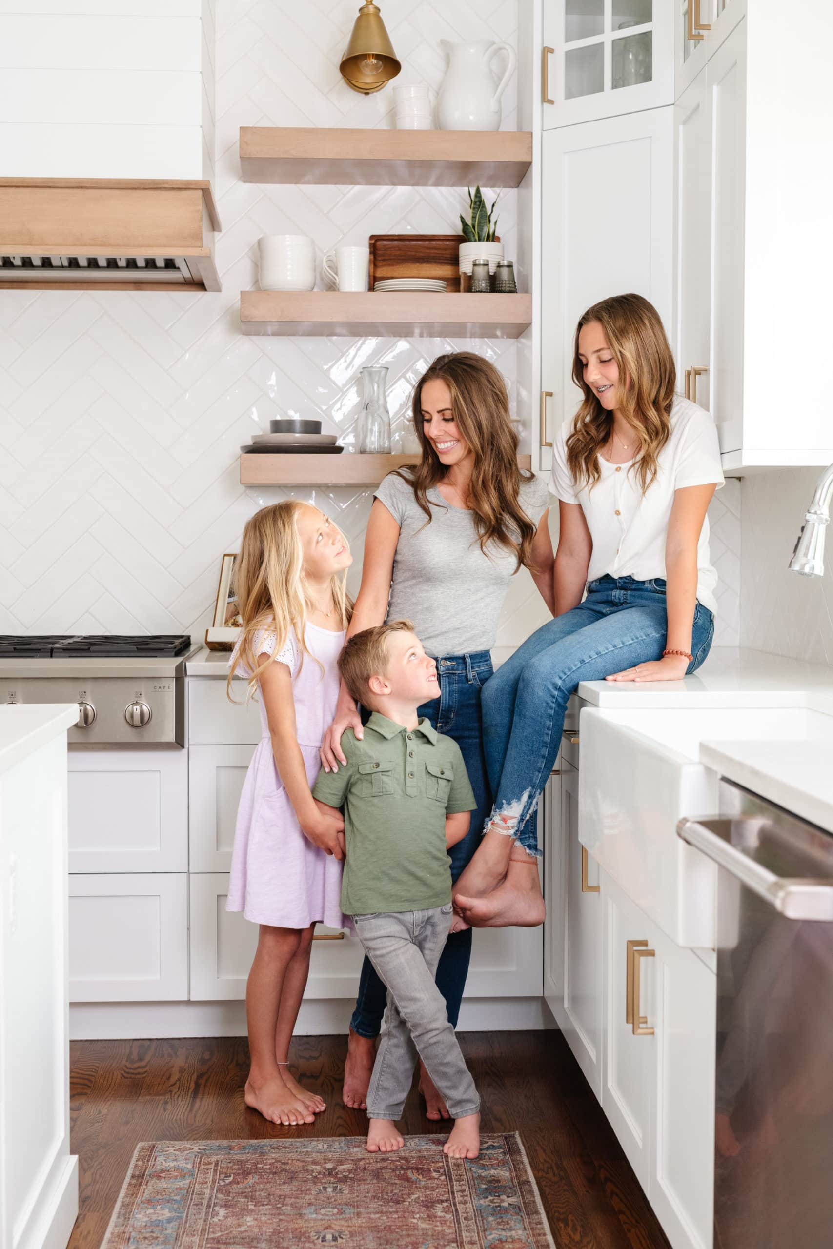 a photo of a mom and her three kids in the kitchen looking at each other