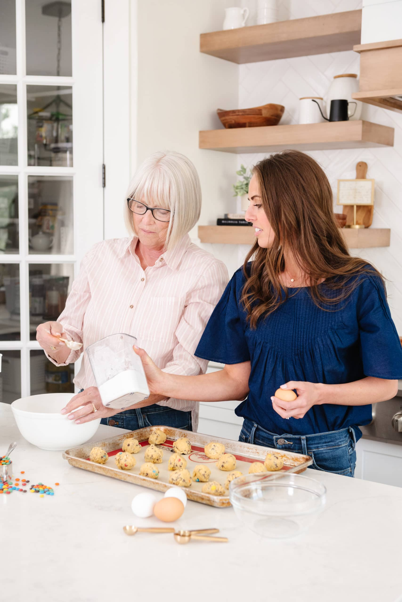 a photo of a mother and her adult daughter making cookies in the kitchen