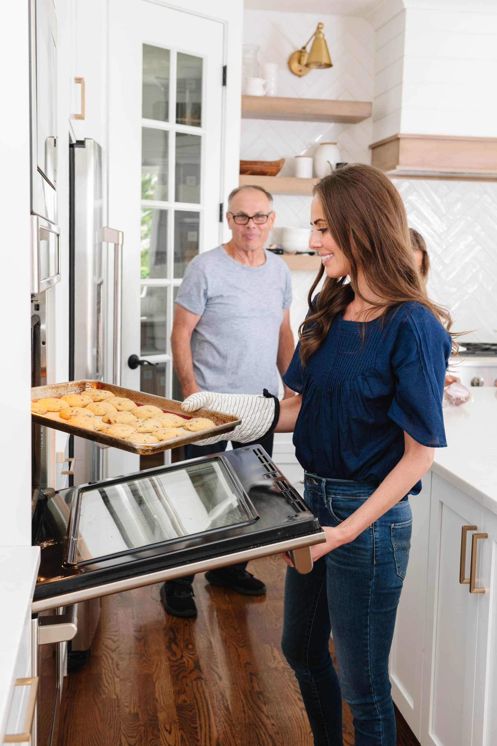 a woman removing a tray of cookies from the oven with her proud father looking on in the background
