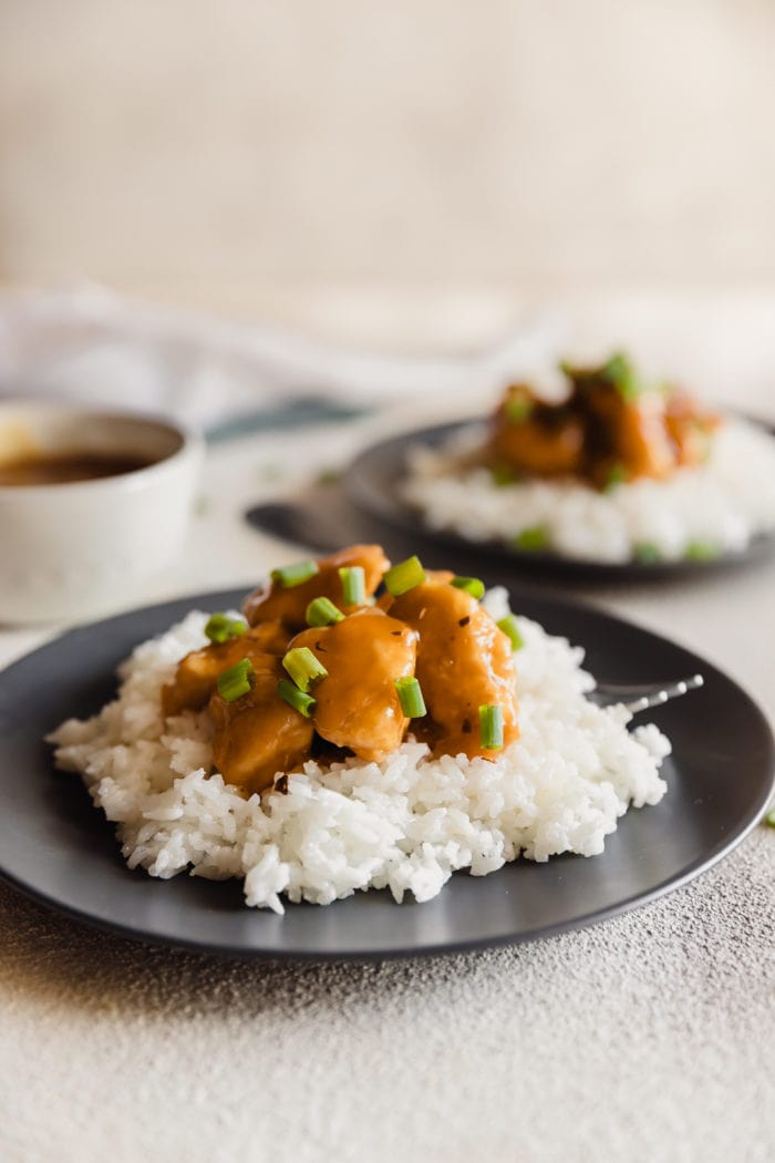 A dark plate with fluffy white rice and orange chicken sprinkled with green onions over the top and a white bowl with extra orange sauce in the background