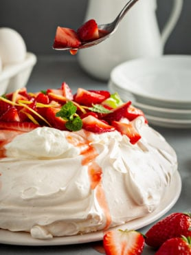 Pavlova on a serving plate. It is topped with whipped cream, sliced strawberries, slivers of lemon rind, and a few mint leaves. A spoon with strawberries and juice drizzling down is above the pavlova. There are white dessert plates, eggs, and a white pitcher are in the background.