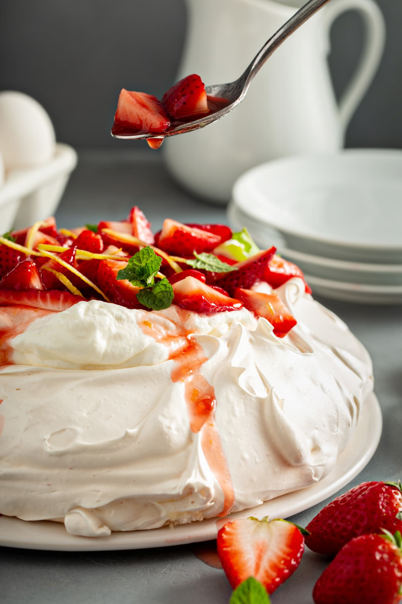 Pavlova on a serving plate. It is topped with whipped cream, sliced strawberries, slivers of lemon rind, and a few mint leaves. A spoon with strawberries and juice drizzling down is above the pavlova. There are white dessert plates, eggs,