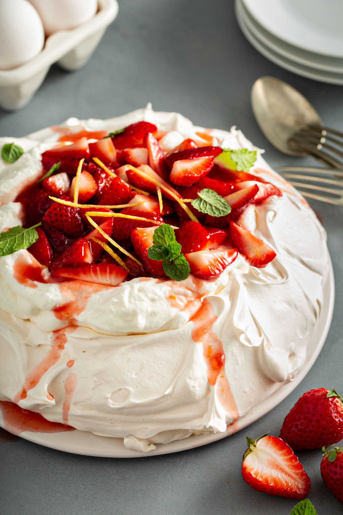 Pavlavo topped with whipped cream and sliced strawberries. A few strawberries and a spoon are on the table next to the pavlova.