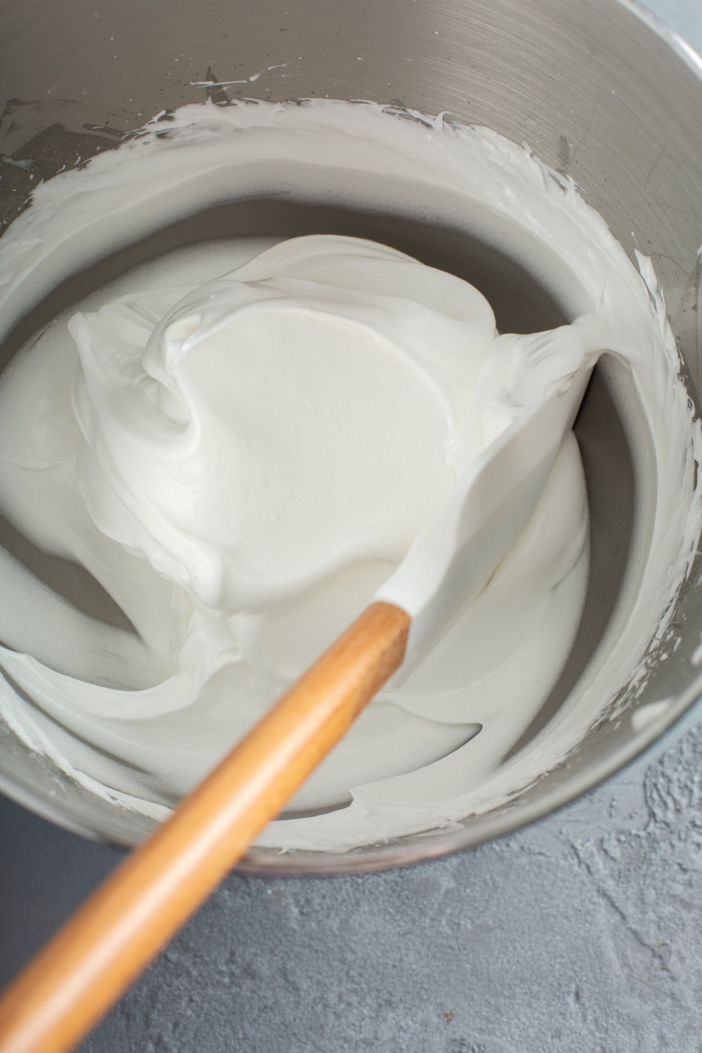 A mixing bowl with stiff meringue and a spatula inside.