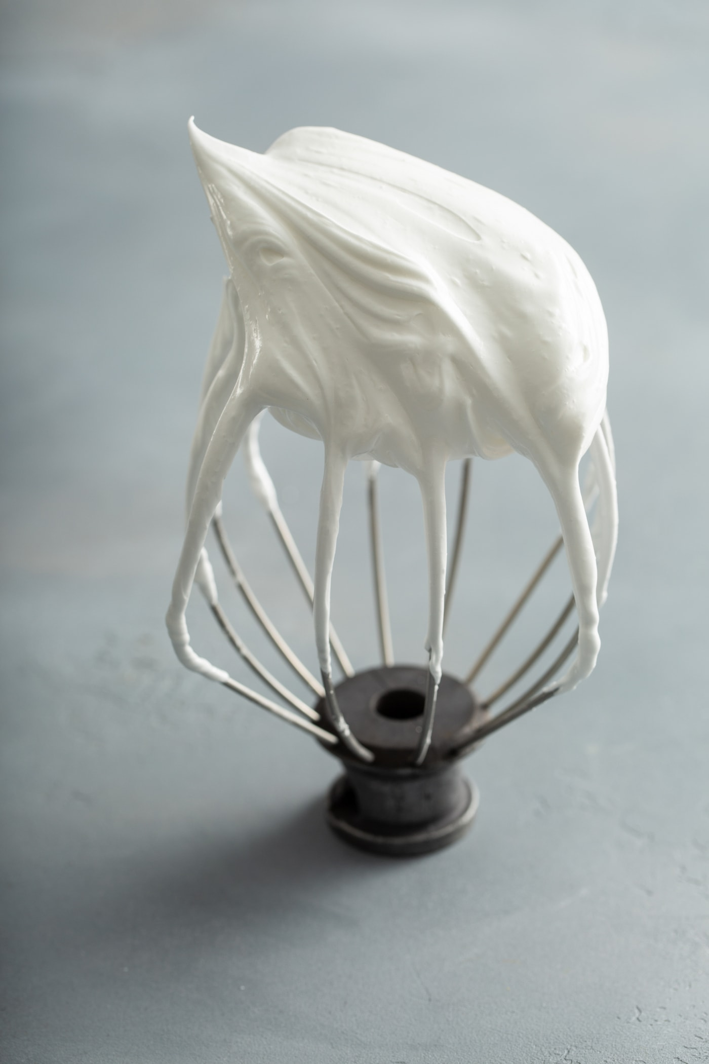 A beater from a stand mixer with firm meringue on the end.
