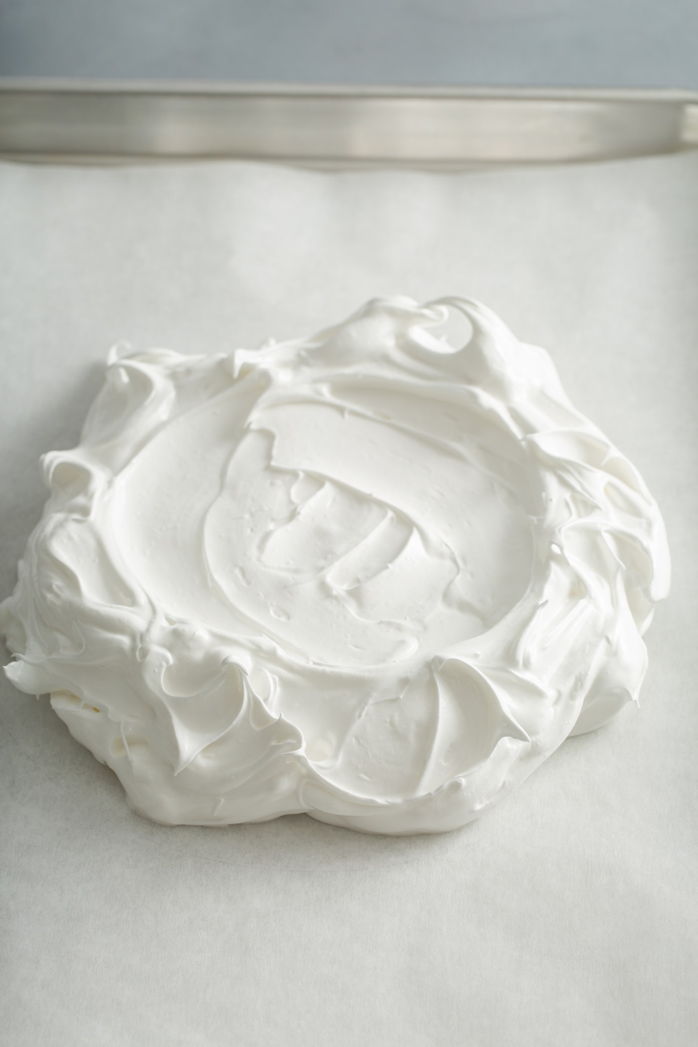 Meringue that has been formed into a disk with a few fancy swirls and peaks.