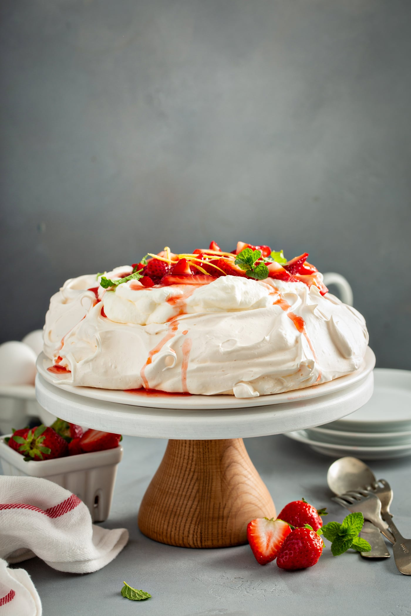 A cake platter holding pavlova that has been topped with sliced strawberries, slivers of lemon rind, and mint leaves. There are three white dessert plates, a carton of eggs, a container of strawberries, red striped kitchen towel and forks and spoons laying on the table around the platter of pavlova.