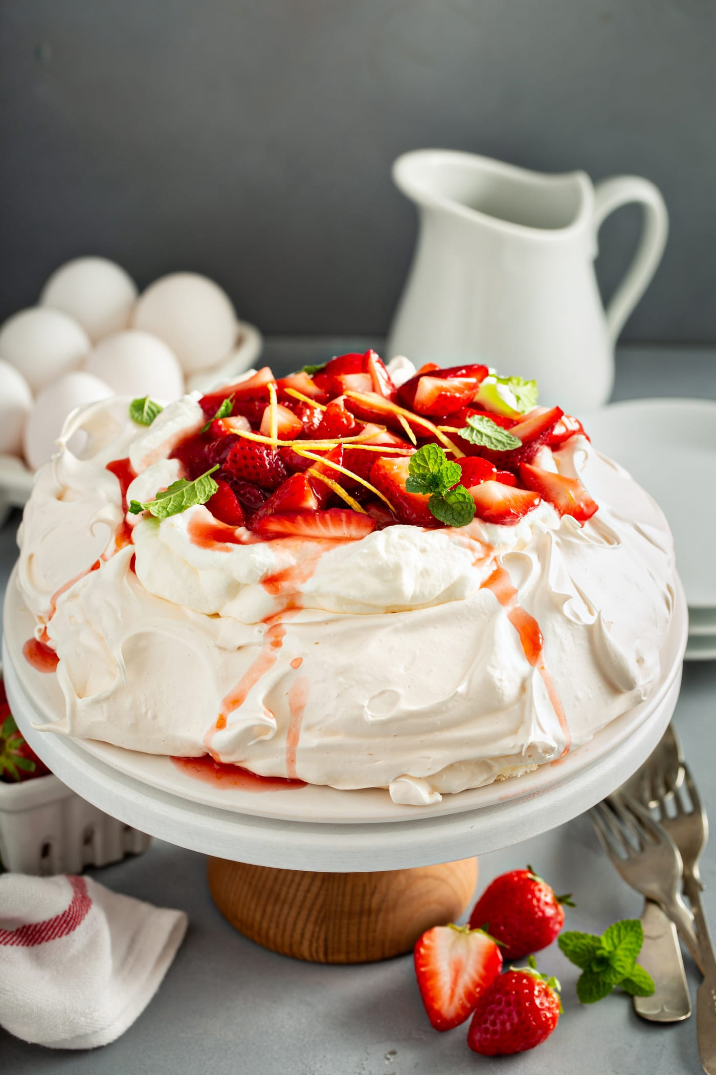 A serving plate containing pavlova topped with fresh whipped cream and sliced strawberries with slivers of lemon rind and mint leaves. There is a carton of white eggs, a carton of white eggs, a white pitcher and a stack of white dessert plates are in the background.