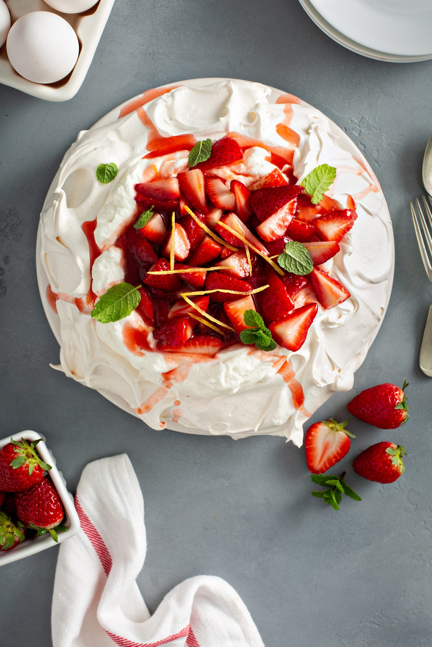 Pavlova topped with whipped cream, sliced strawberries, slivers of lemon rind, and mint leaves. There is a container of strawberries, three strawberries laying next to the pavlova and a fork and spoon.