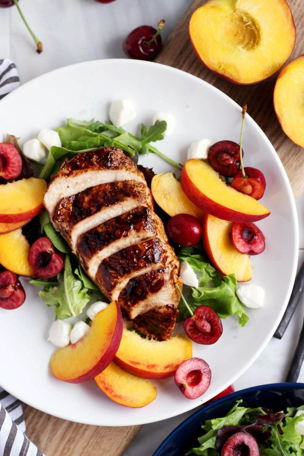 This peach caprese salad with balsamic glazed grilled chicken is a fresh new spin on your classic caprese salad with fresh peaches, cherries and mozzarella paired with perfectly grilled balsamic chicken! Easy Peach Caprese Salad with Grilled Balsamic Chicken - a light and flavorful summer salad with is healthy and ready in 30 minutes!
